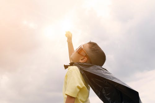 Kid with a cape looking at the sky